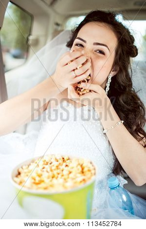 Wedding portrait of bride greedily eating popcorn in car
