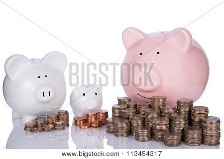 Three piggy banks, small medium large with money