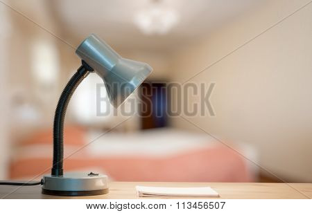 lamp and notebook on table in the bedroom