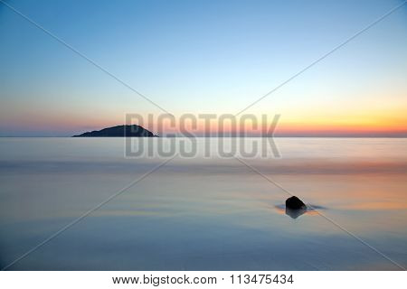 Motion Blur Of The Sea Under Vivid Twilight Sunset Sky With Long Exposure Effect.