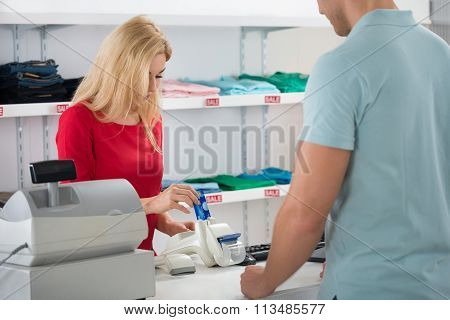 Cashier Using Credit Card While Standing With Customer
