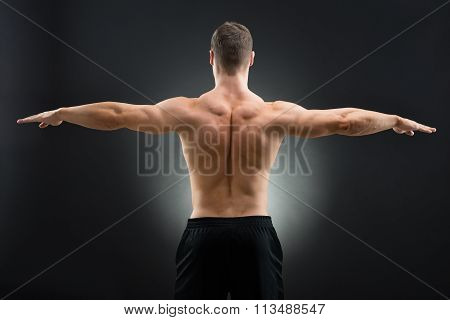 Rear View Of Muscular Man Standing Arms Outstretched
