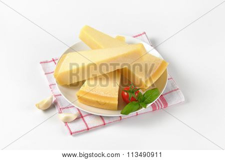 three wedges of fresh parmesan cheese on white plate and checkered dishtowel