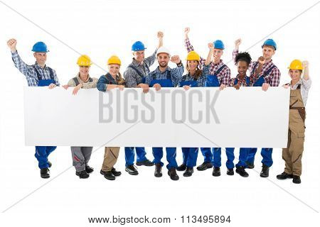 Happy Carpenters With Arms Raised Holding Blank Billboard