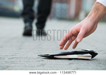 Businessman Picking Up Fallen Wallet With Money