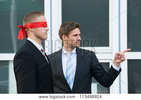 Businessman Assisting Blindfolded Partner