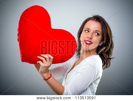 Playful Young Woman Holding A Red Heart
