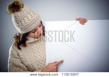 Young Woman In Winter Fashion Pointing To A Sign