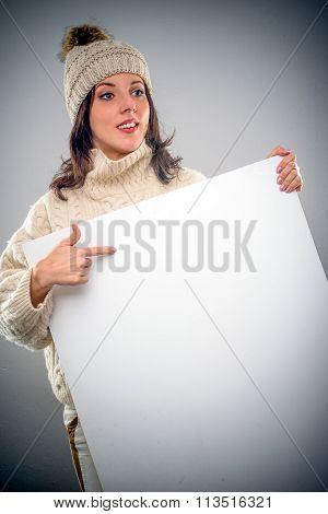 Pretty Young Woman Pointing To A Blank Sign