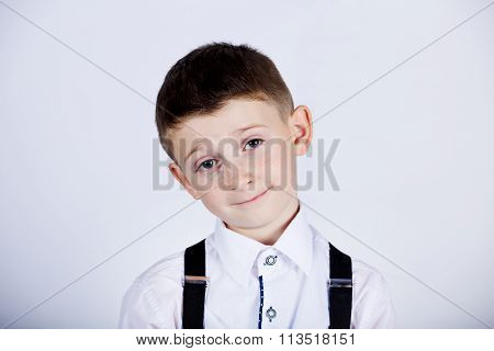 Funny emotion of little boy young man with a raised eyebrow wearing costume with braces