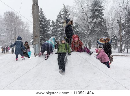 Makeevka, Ukraine - January 07, 2016: Children Playing On A Snowy Hill On A Central Square