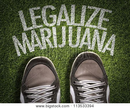 Top View of Sneakers on the grass with the text: Legalize Marijuana