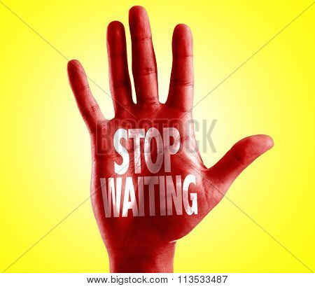 Stop Waiting written on hand with yellow background