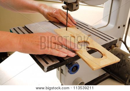 Closeup of a woman's hands working with a band saw to cut an intricate shape in a piece of plywood