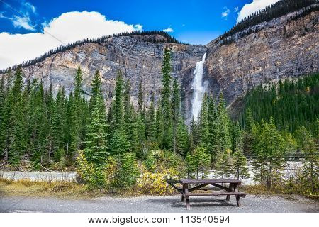 Waterfall Takakkaw in Yoho National Park in the Rocky Mountains. Comfortable wooden table and benches for a picnic