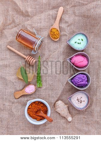 Alternative skin care and homemade scrubs with natural ingredients sage turmeric sea salt honey aloe veralemon rosemarymint and sesame on brown cloth sack background. poster