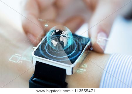 close up of hand with globe hologram on smartwatch