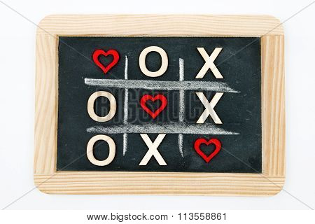Vintage chalkboard with Tic Tac Toe Game Competition XO Win created of wood letters and red hearts letters O and X replaced with red heart shapes isolated on white Love Always Wins Concept poster