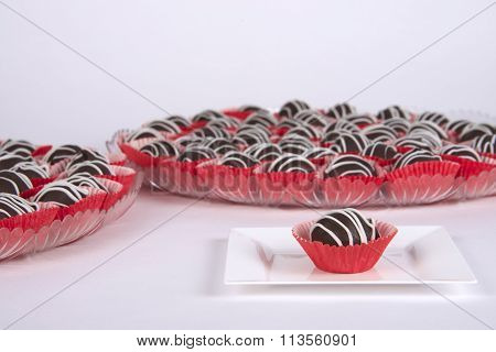 Chocolate Cake Balls in red cupcake liners presented on serving trays