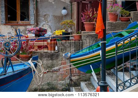 Two blue and green boats sitting on land in small italian town Scilla
