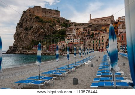 Blue umbrella and beachchair at  the beach in front of small italian town on cliff under blue sky