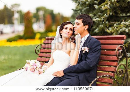 The bride and groom sitting on a bench in the Park