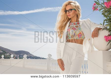 Beautiful blond hair sexy woman young girl model in sunglasses and elegant color with crystals sweatshirt top around the pool with a balustrade overlooking the sea and the island of Santorini