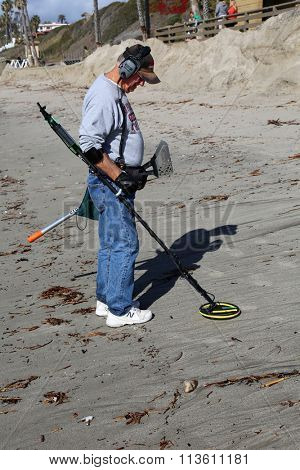 San Clemente CA Jan. 7 2016: A man uses his Metal Detector as he sifts through the sand after the Godzilla El Nino of 2016 hits the beach of San Clemente CA in hopes of finding lost buried treasure