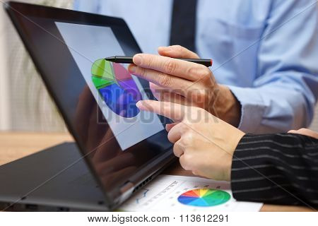 Business Team Is Working  During Meeting On Report With Financial Diagram On Laptop Screen, Pointing