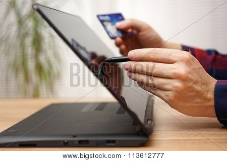 Man Is Using Debit Or Credit Card To Pay Online On Portable Touchscreen Laptop Computer With Pen