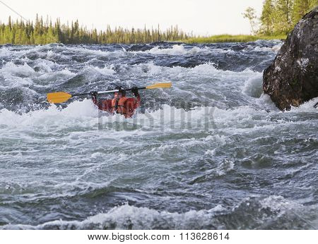 Kayaker turning over in whitewater
