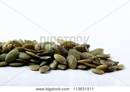 closeup view of pumpkin seeds on a bright background