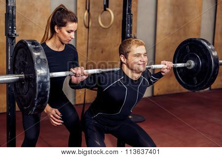 Closeup trainer girl assisting in squat exercise