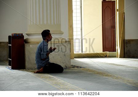 A man pray in Sultan Abu Bakar State Mosque in Johor Bharu, Malaysia