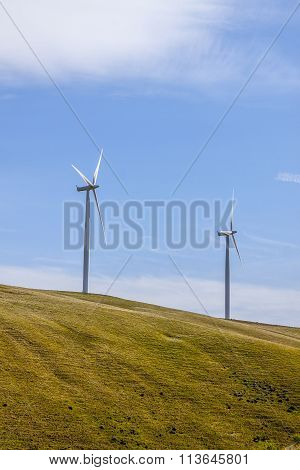 renewable energy source from windmills on sunny landscape