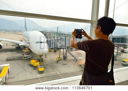 HONG KONG - NOVEMBER 03, 2015: man taking photo of the Airbus A380. The Airbus A380 is a double-deck, wide-body, four-engine jet airliner manufactured by the European aircraft company Airbus