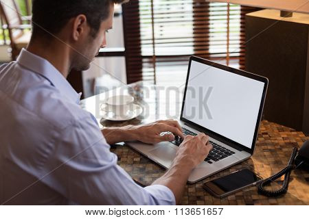 Man working on laptop in home interior