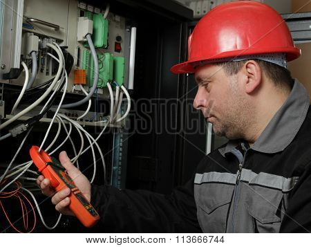 Worker In Red Helmet Make Electrical Measurements
