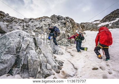 Group Of Climbers Ascent To The Mountain On A Complex Slope Is Composed Of Rock And Snow