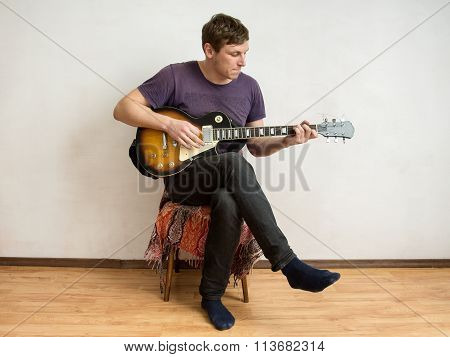 A Man In A Purple Shirt Playing Guitar