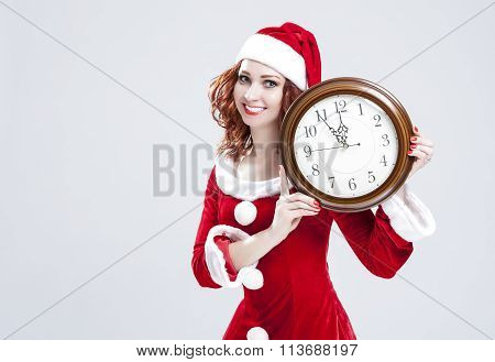 Time And Christmas Holiday Concept. Smiling And Gleeful Red-haired Santa Helper Showing Time On Big