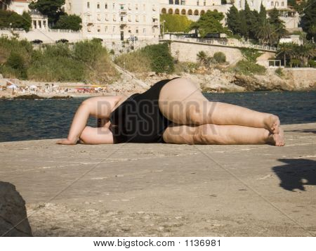 fat obese woman sleeping outdoors in the sun