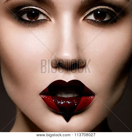 Creative portrait of beautiful young girl with a black heart painted on her red lips
