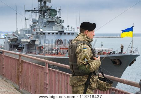 Odesa, UKRAINE - MARCH, 26, 2015: Ukrainian soldier stands on a background of the warship Hetman Sag