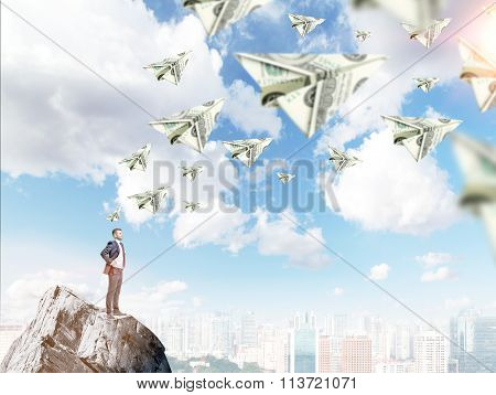 Young man standing on the rock with hands on hips thinking about money and opportunities dollar planes flying around. City panorama at the background. Concept of getting a fortune. poster