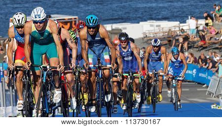 Stuggling, Muscular Triathlon Competitors Cycling Uphill