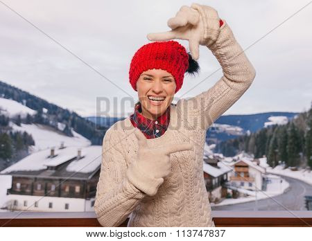 Happy Woman Framing With Hands On Balcony Overlooking Mountains
