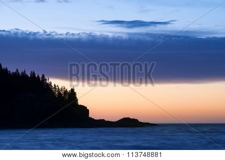 Rocky Coastline with Colorful Sunrise and Cloud Layers