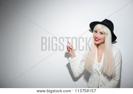 Cheerful young woman is showing something confidently
