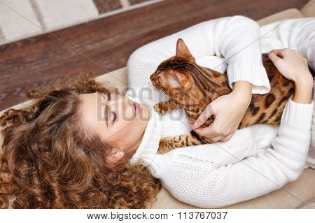 Girl And A Cat Lying On The Sofa. Hugs .